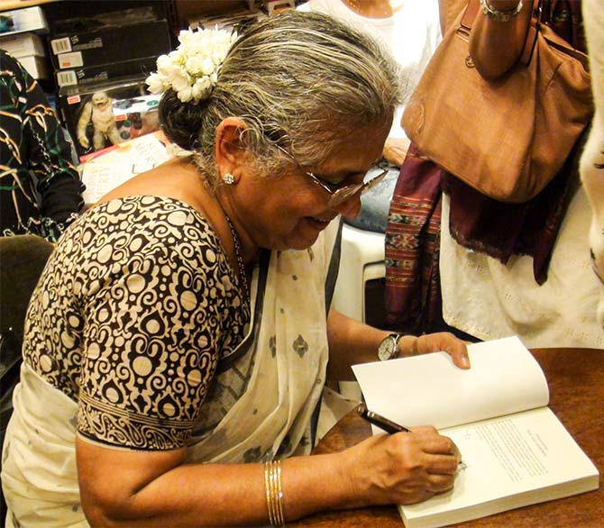 Sudha Murty signs a copy of her book, The Serpent's Revenge