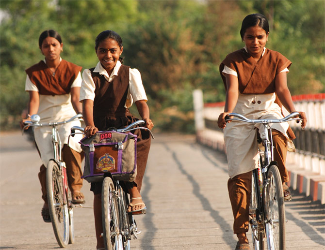 Young girls cycling to school