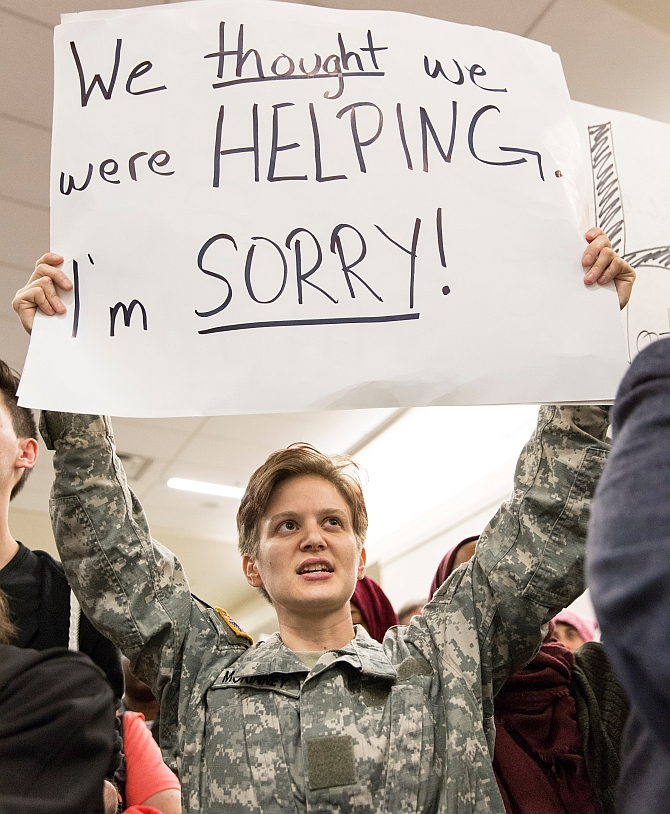 A US military veteran holds a sign as people protest Donald Trump's travel ban at Dallas/Fort Worth International Airport, Dallas, Texas, January 29, 2017. Photograph: Laura Buckman/Reuters