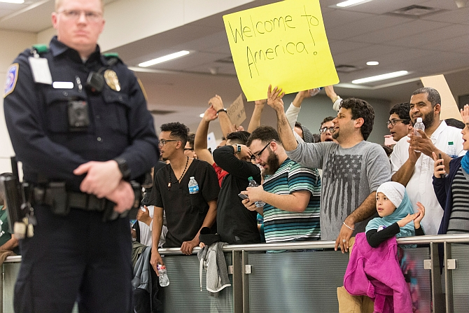 A man holds a welcome sign as people protest against the travel ban imposed by Trump's executive order at the Dallas/Fort Worth International Airport in Dallas, Texas, January 29, 2017. Photograph: Laura Buckman/Reuters