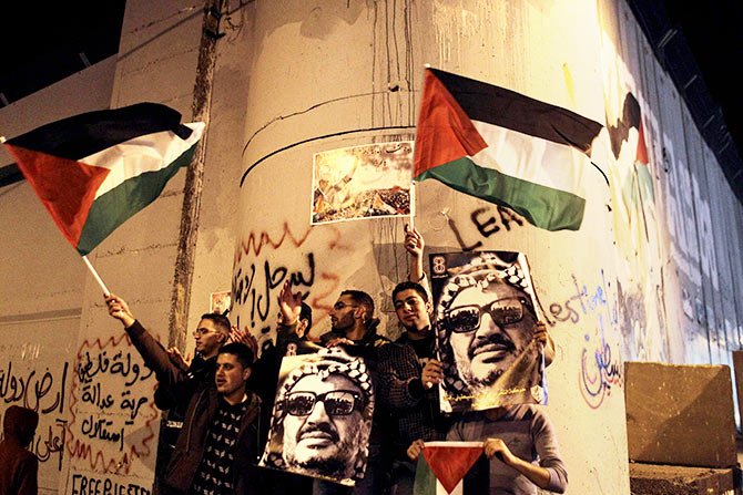 Palestinians with posters of the late Palestinian leader Yasser Arafat and Palestinian flags during a rally