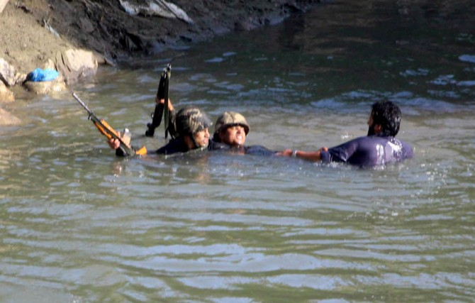 Soldiers capture a stone pelter from a lake around the encounter site in Kashmir, June 16, 2017. Photograph: Umar Ganie