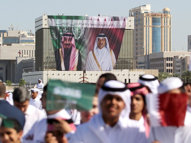 A poster shows Saudi King Salman and Qatar's Emir Sheikh Tamim Bin Hamad Al-Thani as people wave Qatari and Saudi flags during a welcoming ceremony for King Salman at the Royal Court on Doha Corniche, Qatar, December 5, 2016. Photograph: Naseem Zeitoon/Reuters