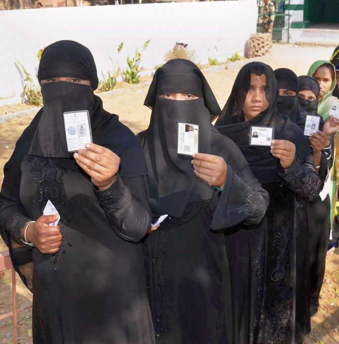 Muslim women queue up at a polling booth