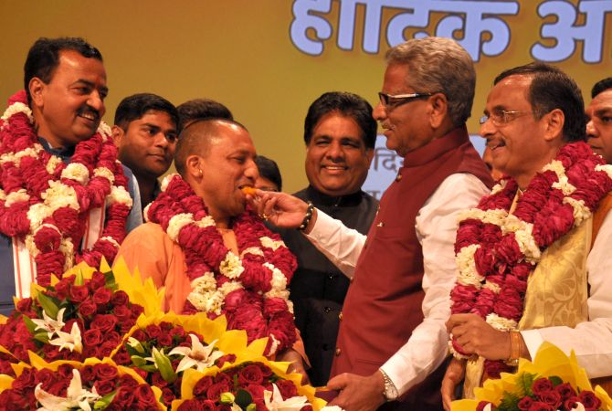 BJP General Secretary O P Mathur feeds Yogi Adityanath a sweet after his election as leader of the BJP legislature party in UP, March 18, 2017, as Deputy Chief Ministers-elect Keshav Prasad Maurya, left, and Dr Dinesh Sharma, right, look on. Photograph: Sandeep Pal