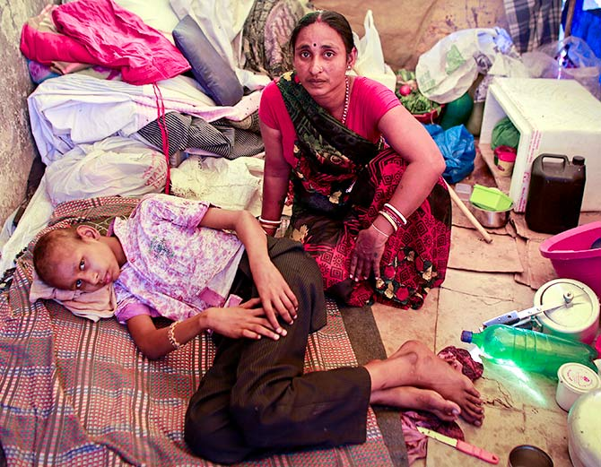 In this photograph shot on March 4, 2013, Raj Kishore Kumar, a 12-year-old cancer patient, rests with his mother inside his pavement dwelling outside the Tata Memorial Hospital in Mumbai. Photograph: Danish Siddiqui/Reuters