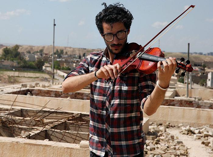 Ameen Mukdad, a violinist from Mosul, Iraq, who lived under ISIS rule for two-and-a-half years where they destroyed his musical instruments, performs at the Nabi Yunus shrine in eastern Mosul, April 19, 2017, after the town was liberated. Photograph: Muhammad Hamed/Reuters