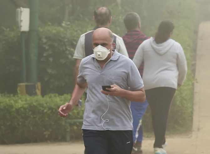A man wearing an anti-pollution mask jogs through smog at Lodhi Garden, New Delhi. Photograph: Kamal Kishore/PTI Photo