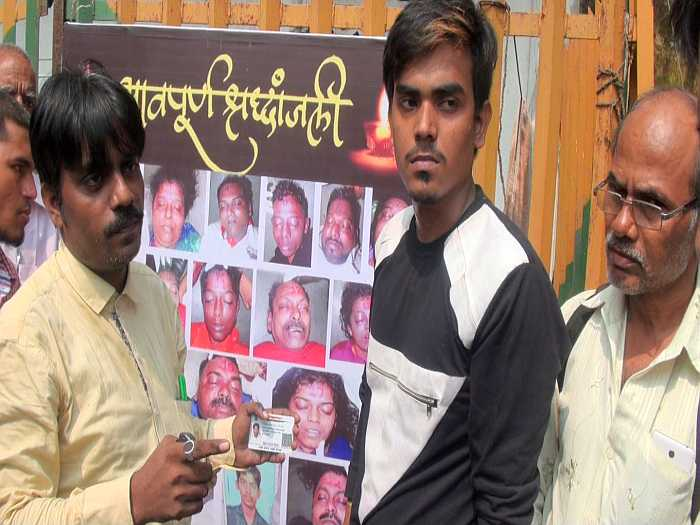 Shaikh Mohammed Shakil's elder brother Sadiq (in yellow) showing his Aadhar card to prove that his brother's photograph in the collage behind him, and numbered 18, was not his brother. Taamil (in black tee), who is elder to Shakil, also works in one of the garment outlets at Elphinstone Road station