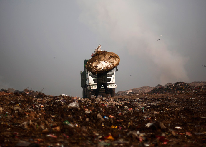A man carries a sack of recyclable material at a garbage dump in New Delhi February 2, 2014. Photo: Adnan Abidi/Reuters