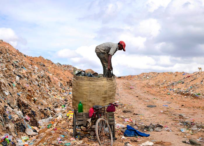 A rag picker prepares to pack a sack filled with recyclable materials, mounted on his tricycle at a garbage dump on the outskirts of the southern Indian city of Bangalore August 26, 2014. Photo: Abhishek N Chinnappa/Reuters