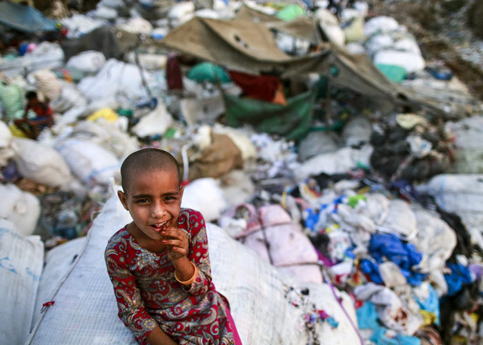 A girl sits on a sack of discarded clothes at a slum in Mumbai, India, April 20, 2016. Photo: Danish Siddiqui/Reuters