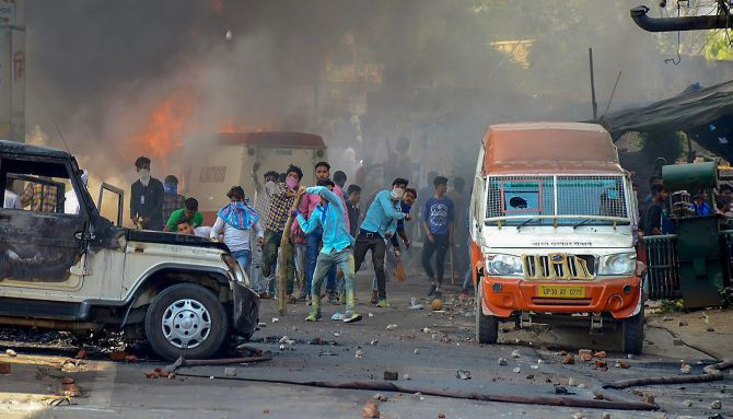 During the Bharat Bandh, April 2, 2018, protesters hurl brickbats as smoke billows out of burning cars in Muzzaffarnagar, Uttar Pradesh. Photograph: PTI Photo