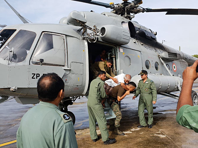 Elderly being carried by IAF personnel