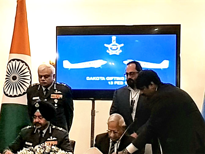 Air Commodore M K Chandrasekhar (retd) and Air Chief Marshal Birender Singh Dhanoa sign the gift deed as Air Marshal Shirish Baban Deo, the vice chief of the air staff, left, and Rajeev Chandrasekhar look on