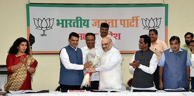 Union Minister Nitin Gadkari, seen right, as Bharatiya Janata Party President Amit Anilchandra Shah felicitates Maharashta Chief Minister Devendra Fadnavis in Mumbai, July 22, 2018. Photograph: Arun Patil