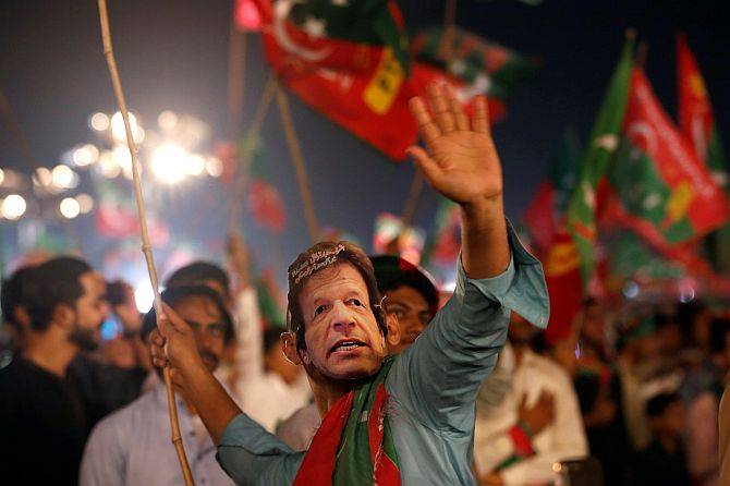 A supporter of Imran Khan wears a mask of the Pakistan Tehreek-e-Insaf leader and dances to party songs during a campaign rally July 22, 2018. Photograph: Akhtar Soomro/Reuters