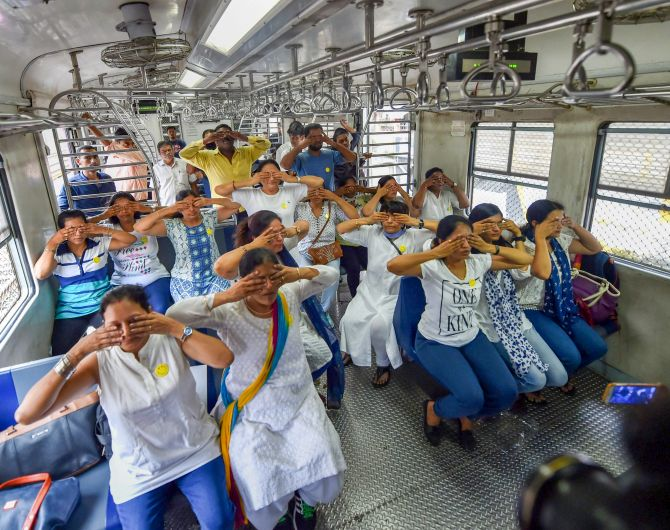 Commuters practise yoga in a local train in Mumbai.