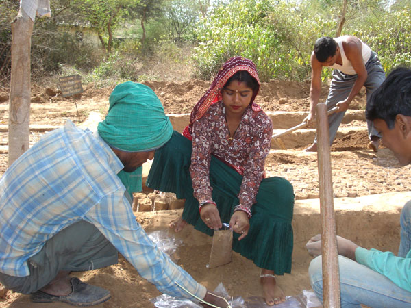 Locals filling soil in bags for distribution of the saplings