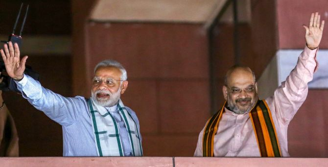 Prime Minister Narendra D Modi and Bharatiya Janata Party President Amit A Shah wave to party workers gathered at the BJP headquarters after the Karnataka assembly election result, May 15, 2018. Photograph: PTI Photo
