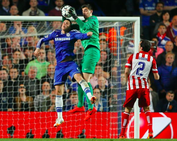 Atletico Madrid's goalkeeper Thibaut Courtois saves in front of Chelsea's Fernando Torres