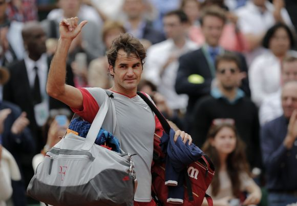 Roger Federer of Switzerland waves to the crowd as he leaves the court following his defeat
