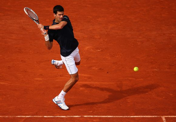 Novak Djokovic of Serbia returns a shot during his men's singles match against Milos Raonic of Canada