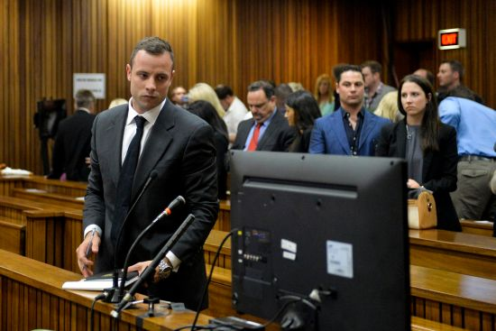 Olympic and Paralympic track star Oscar Pistorius stands in the dock during his trial for the murder of his girlfriend Reeva Steenkamp,