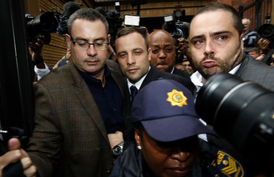 Olympic and Paralympic track star Oscar Pistorius (C) leaves after his trial at the North Gauteng High Court in Pretoria