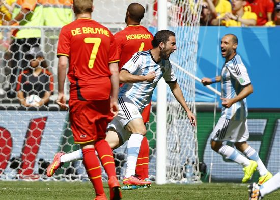 Argentina's Gonzalo Higuain runs past Belgium's Kevin De Bruyne (7) and Vincent Kompany to celebrate after scoring a goal