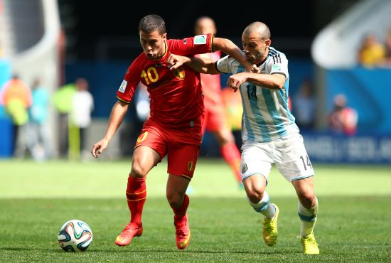 Eden Hazard of Belgium holds off the challenge of Javier Mascherano of Argentina