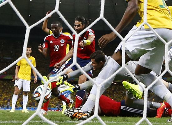 Brazil goalkeeper Julio Cesar tries to stop an an attempt at goal by Colombia's Mario Yepes (No 3)