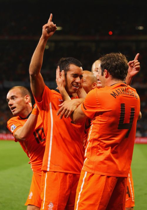Giovanni Van Bronckhorst of the Netherlands celebrates scoring the opening goal with his Dutch team mates.