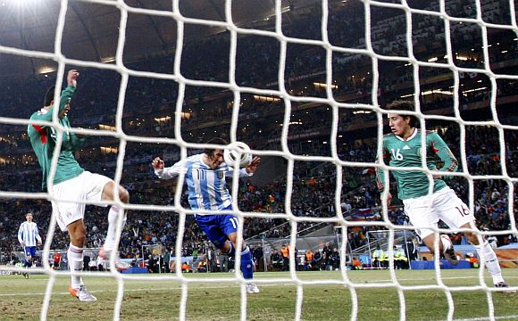 Argentina's Carlos Tevez (centre) scores a goal past Mexico's Efrain Juarez (right) and Francisco Rodriguez