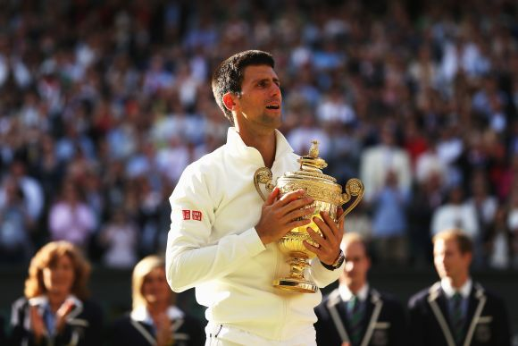 Novak Djokovic of Serbia poses with the Gentlemen's Singles Trophy following his victory against Roger Federer