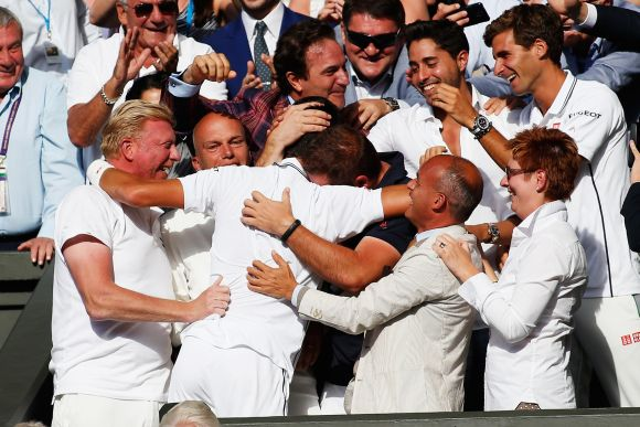 Novak Djokovic of Serbia celebrates in his player's box with friends, family and coach Boris Becker