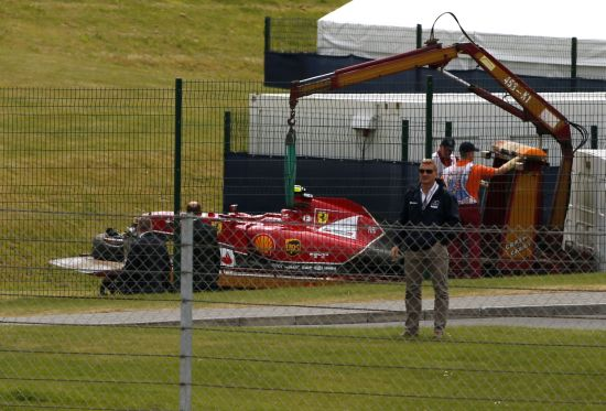 The car of Ferrari Formula One driver Kimi Raikkonen of Finland is lifted off the track following a crash