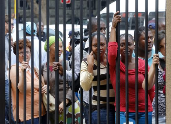 Bystanders look through a fence hoping to catch a sight of Olympic and Paralympic track star Oscar Pistorius