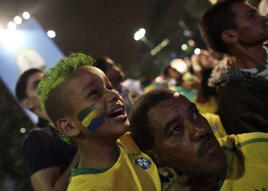 A Brazilian boy fan cries next to his father