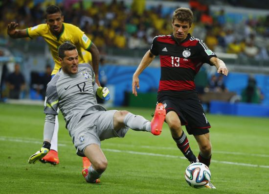 Brazil's goalkeeper Julio Cesar (L) fights for the ball with Germany's Thomas Mueller