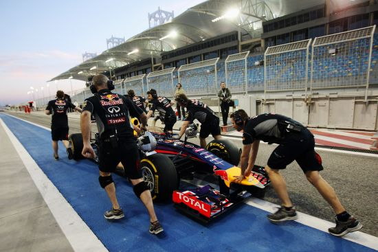 The car driven by Sebastian Vettel of Germany and Infiniti Red Bull Racing suffers a fault and is pushed back along the pitlane by team mates