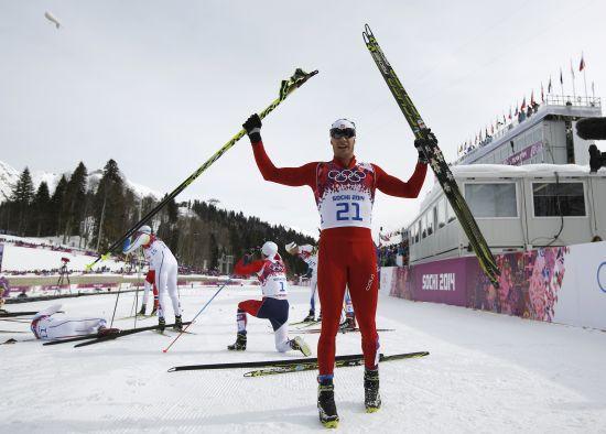 Dario Cologna celebrates after winning men's skiathlon