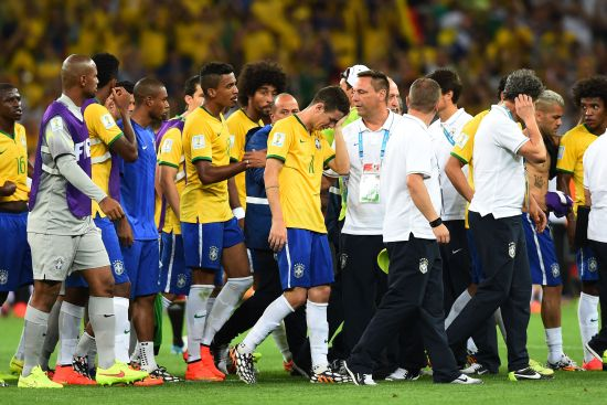 Oscar of Brazil (center) reacts with teammates after being defeated 7-1 by Germany