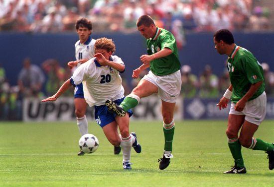 Roy Keane of Ireland kicks the ball as Giuseppe Signori of Italy tries to break it up