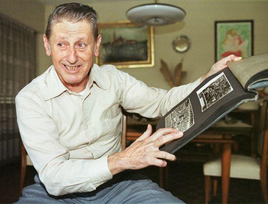 Former Uruguayan striker Juan Schiaffino is seen showing old pictures of Maracana stadium