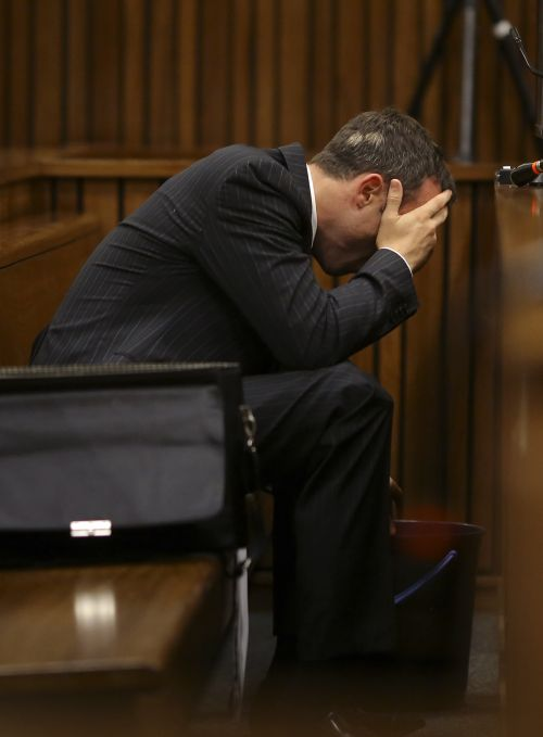 Olympic and Paralympic track star Oscar Pistorius reacts as he reaches for a bucket in the dock during his trial for the murder of his girlfriend Reeva Steenkamp