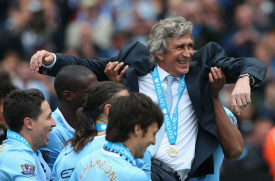 The Manchester City Manager Manuel Pellegrini is lifted up by his players