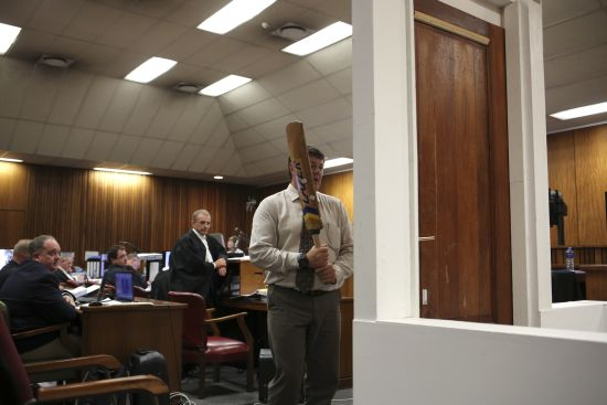 A policeman demonstrates the effect of hitting of a bathroom door with a cricket bat during the trial of South African Paralympic athlete Oscar Pistorius in the North Gauteng High Court in Pretoria