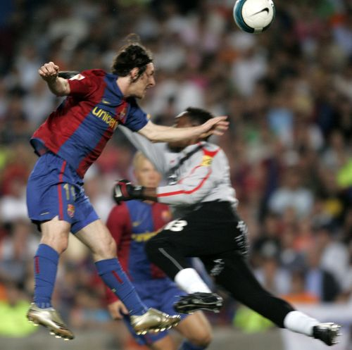 Barcelona's Lionel Messi (left) scores with his hand against Espanyol's goalkeeper Carlos Kameni (right) during their Spanish First Division Soccer League match at Nou Camp Stadium