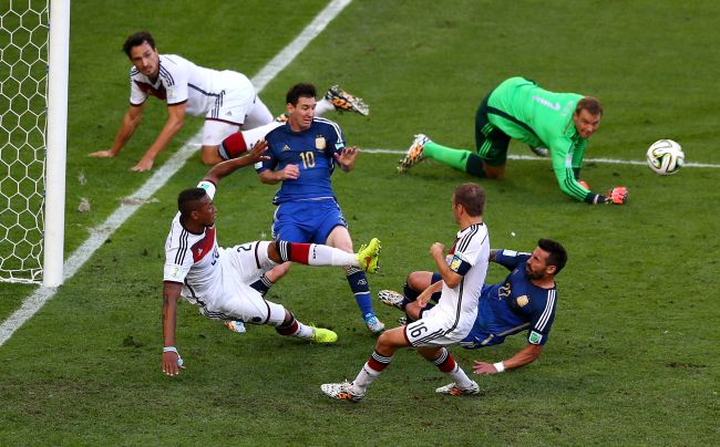 Lionel Messi and Ezequiel Lavezzi of Argentina attempt to shoot as Jerome Boateng of Germany clears the ball off the line